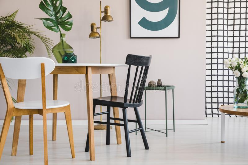 Wooden chair at round table with green leaf in glass vase in fashionable dining room interior with poster on pastel pink wall. Chair at round table with green stock photography