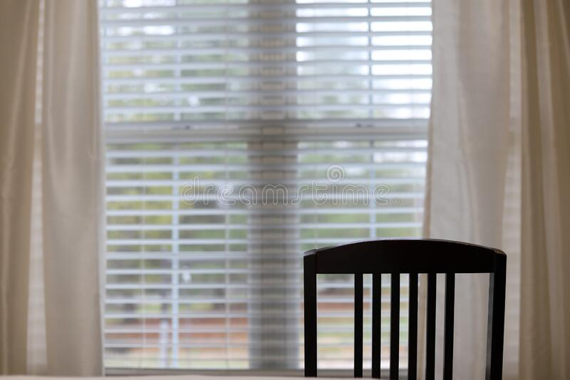 A wooden chair sitting in front of an open window with a view of a backyard. In a house stock image