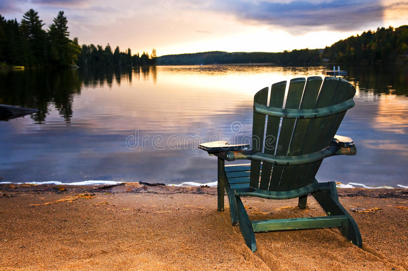 Wooden chair at sunset on beach royalty free stock photos