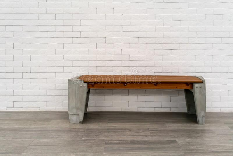 Wooden chair or wood bench with concrete structure inside a building along a walkway. Rest area along pedestrain way stock photo