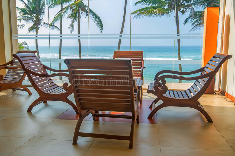 Wooden chairs as part of interior. Detail of interior in colonial style of lounge in tropical resort with view of palms and ocean royalty free stock image