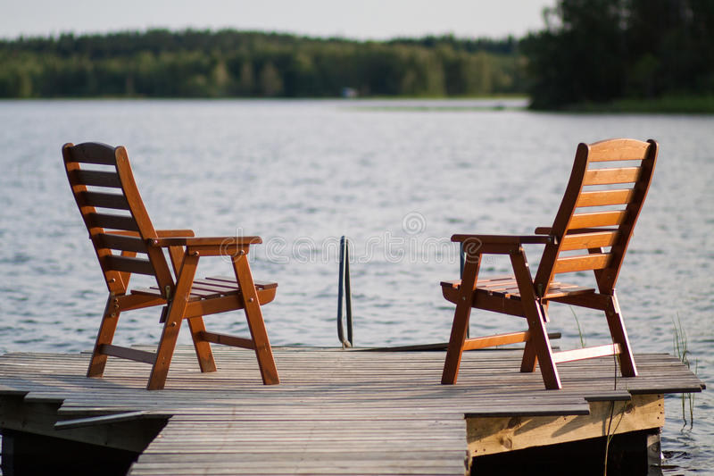 Wooden chairs sitting on the dock stock images