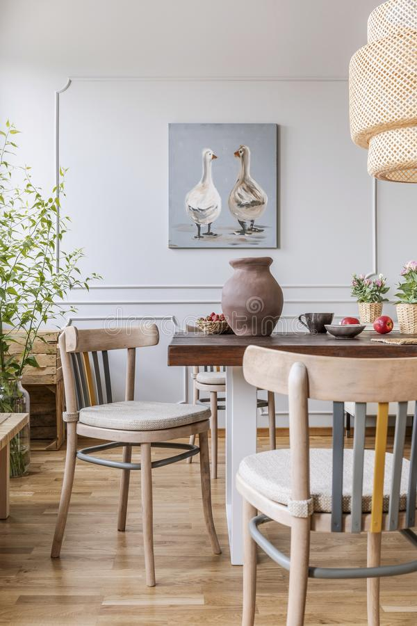 Wooden chairs at table in natural white dining room interior with poster and lamp. Real photo stock image