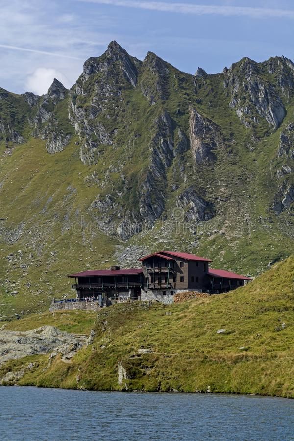 Wooden chalet under the summit on the shores of blue mountain lake. Balea lac mountain lake resort in Carpathians mountains stock image