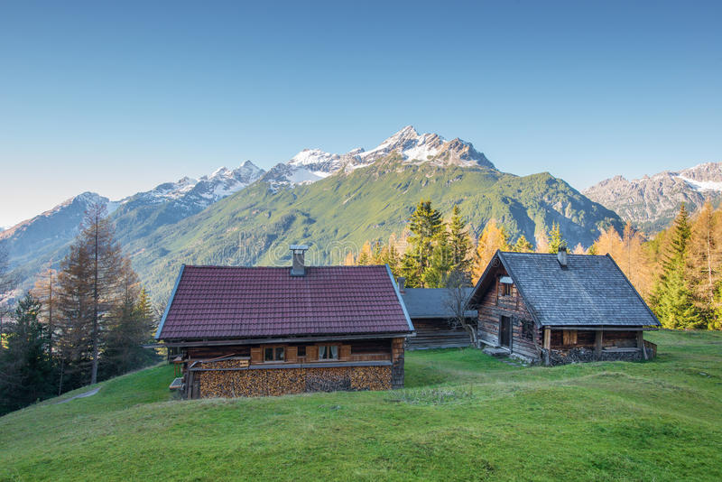 Wooden chalets on mountain meadow. At austrian alps stock image