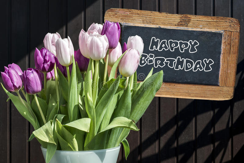 Wooden chalkboard happy birthday Sign beautiful pinktulips bucket spring flowers tulip brown background. Wooden chalkboard happy birthday Sign with beautiful royalty free stock images
