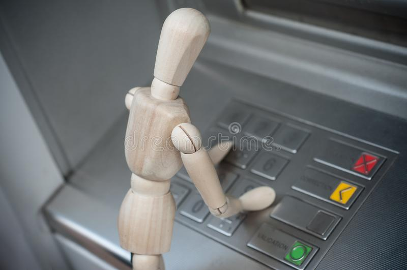 Wooden character at the cash machine in outdoor - concept withdrawal of m. Closeup of wooden character at the cash machine in outdoor - concept withdrawal of stock photo