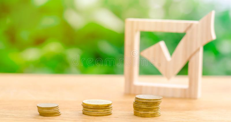 Wooden check mark and stacks of coins. Lobbying the adoption of regulations and laws. Illegal money laundering and control. Of financial flows. Interest rates stock image