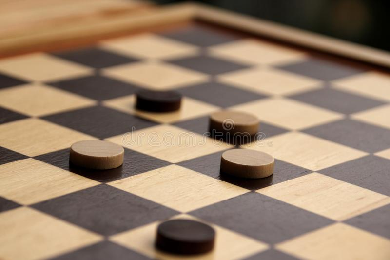 Wooden checkers white and dark brown on a chessboard, game concept royalty free stock photo