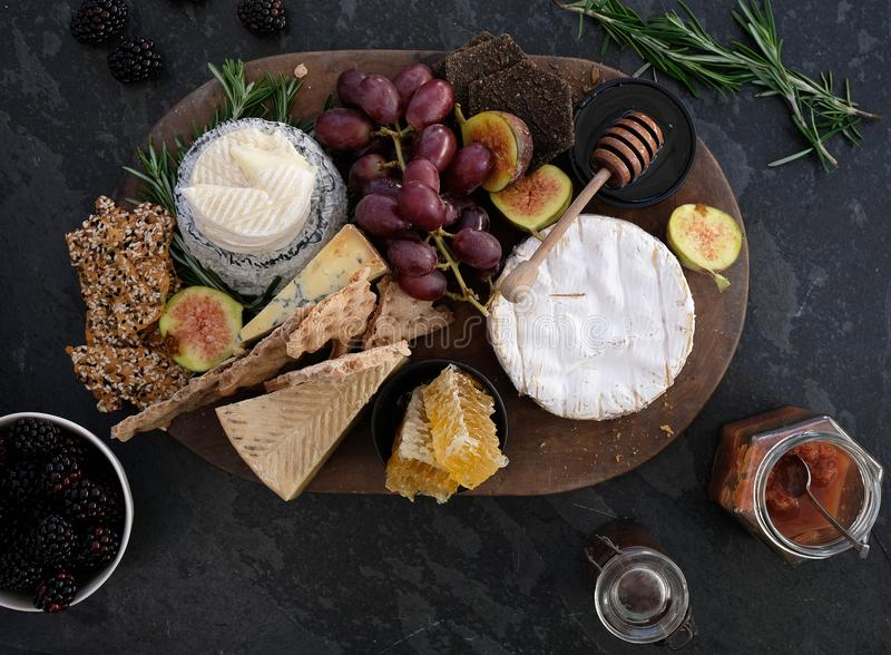 Wooden cheeseboard on slate surface with a variety of cheeses, crackers, fruit, honey, rosemary sprigs and chutney. Wooden cheeseboard on slate surface with a royalty free stock image
