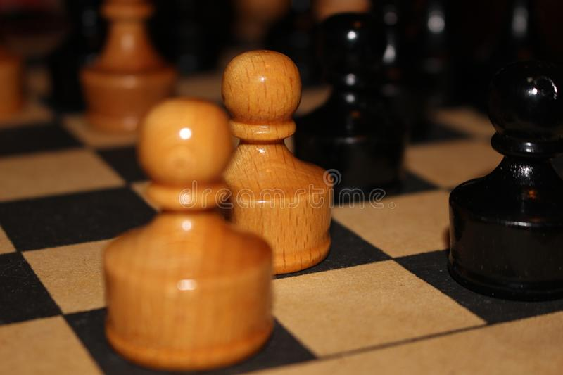 Wooden chess figures. Black and white wooden chess figures on the board royalty free stock photo