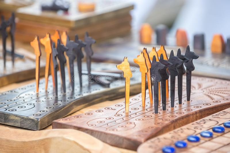 Wooden chess in the form of dogs in the Scandinavian style on the table. Souvenir wooden chess in the form of dogs or wolfs in the Scandinavian style on the royalty free stock photography