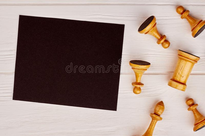 Wooden chess pieces and blank paper sheet. White chess figures and black paper card with copy space stock photography