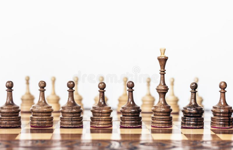 Wooden chess pieces on a chessboard, black queen and white pawns on the background, leadership retro concept.  royalty free stock image