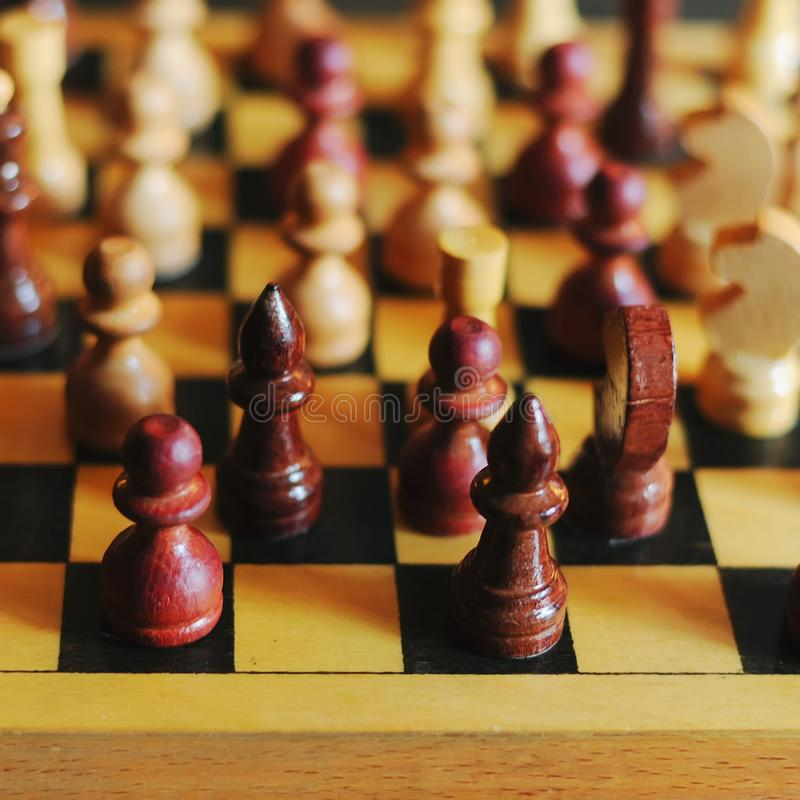 Wooden chess pieces on a chessboard, king in focus stock image