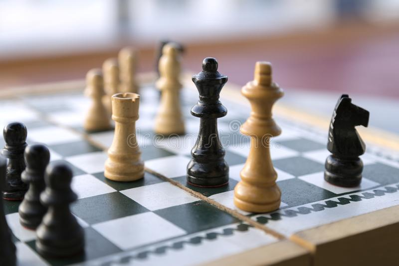 Wooden chess pieces on chessboard royalty free stock photo