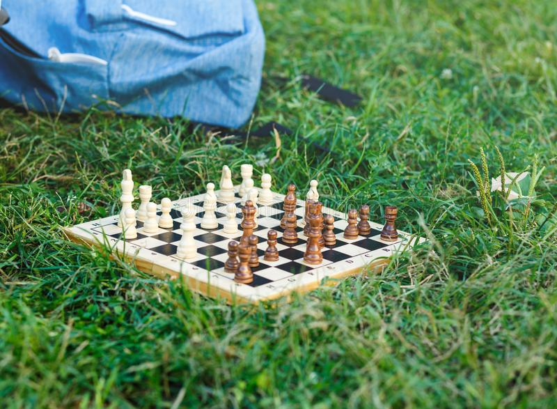 Wooden chessboard with white and brown figures lies on the grass in the park. Hobby, education, intellect stock photos
