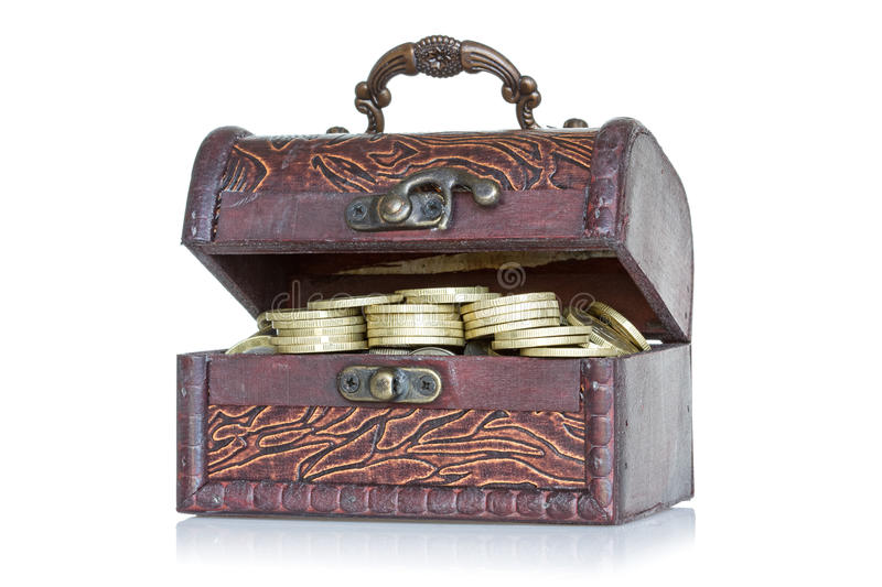 Wooden chest with coins inside. Isolated on white background stock photography