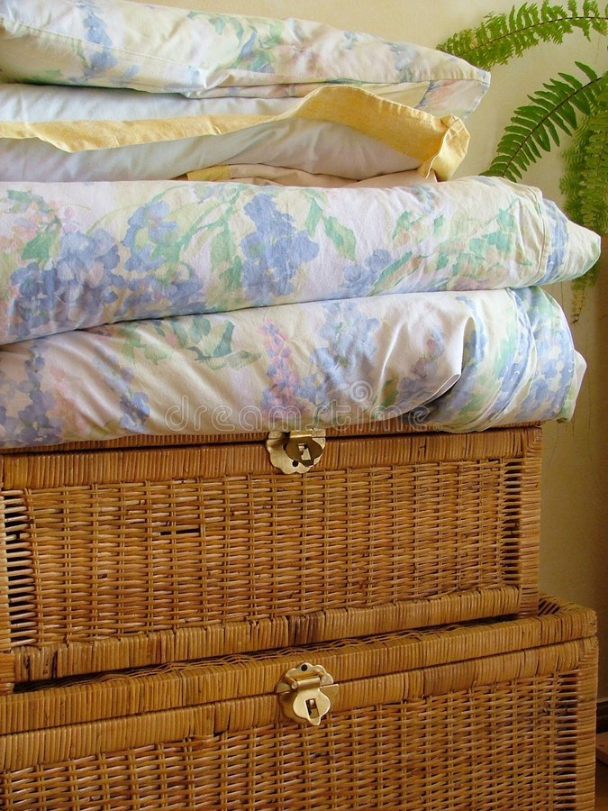 Wooden chest and linens. Wooden chest and bedclothes royalty free stock images