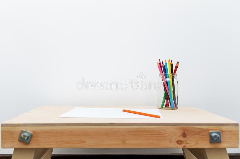 Wooden child drawing table with color pencils by the white wall. With copy space stock photo