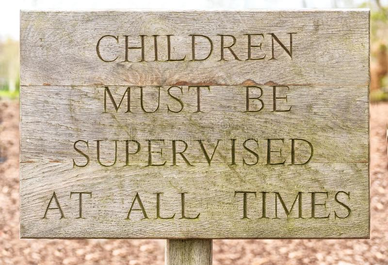 Wooden children must be supervised sign stock photo