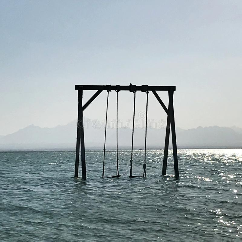 Wooden childrens swing stands in blue calm sea under open clean sky royalty free stock photo