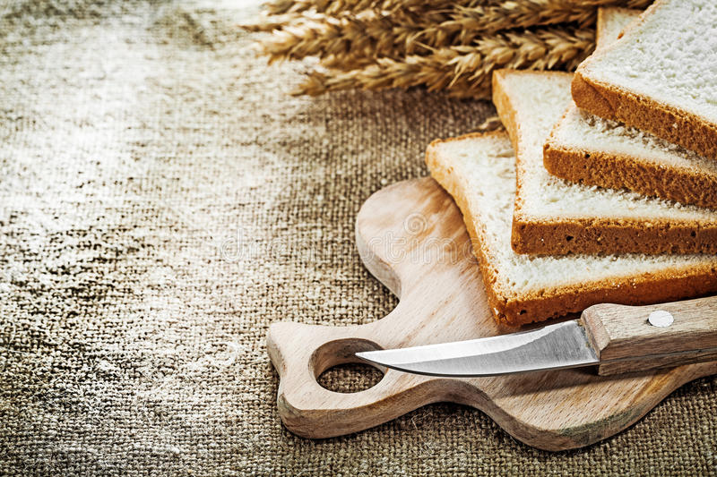 Wooden chopping board knife sliced bread wheat ears on hessian b. Ackground stock images