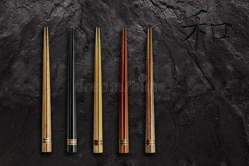 Wooden Chopsticks set on black slate stone. Asian Food Concept royalty free stock image