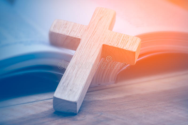Wooden Christian cross. Closeup of simple wooden Christian cross necklace on Bible , vintage tone , god stock photography