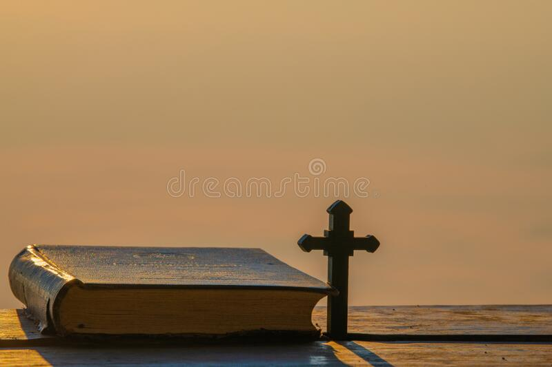 Wooden Christian Cross, Holy Bible Above Wooden Table, Vintage. Window Lighting stock photo