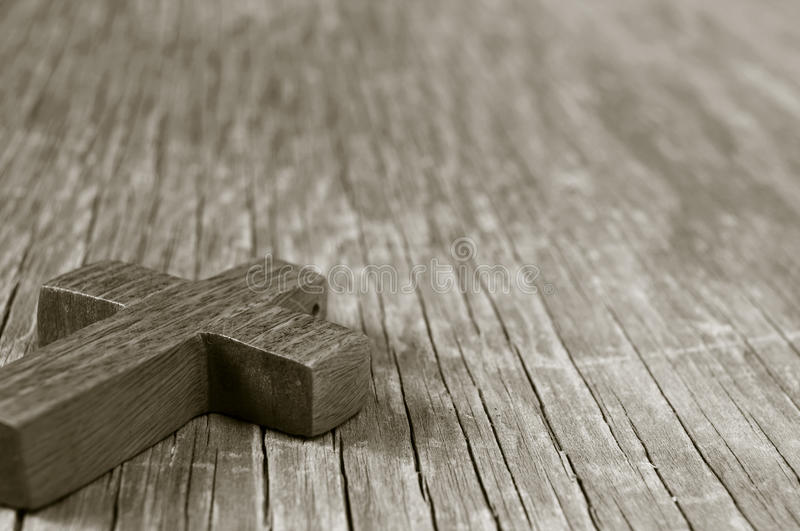 Wooden Christian cross on a rustic wooden surface, sepia toning. Closeup of a wooden Christian cross on a rustic wooden surface, in sepia toning royalty free stock image