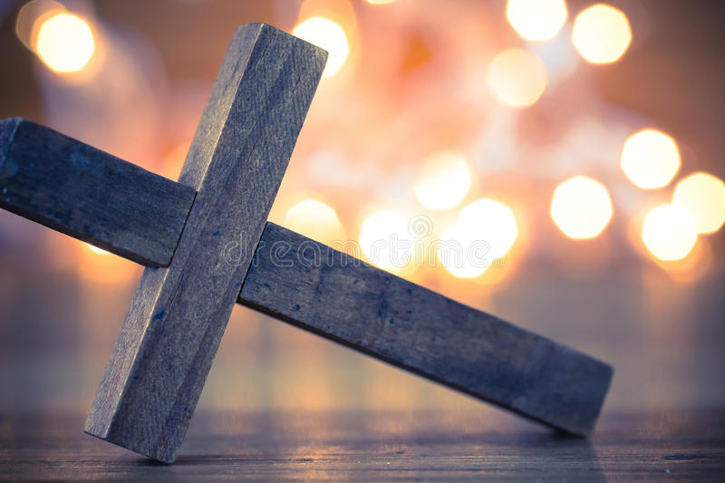 Wooden Christian Cross. A wooden Christian cross with a soft bokeh lights background stock image