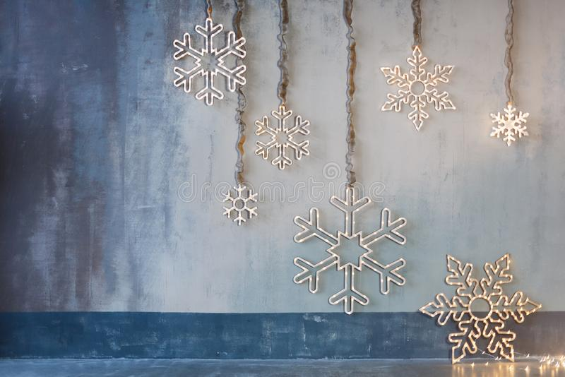 Wooden christmas decoration for the walls. Glowing snowflakes with garland lights on gray concrete background. Christmas stock photography