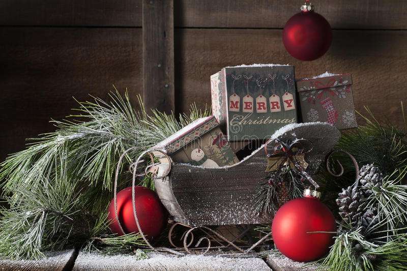 Wooden Christmas Sleigh. A wooden Christmas sleigh filled with vintage boxes, one with Merry Christmas greeting. Evergreen pine boughs are around and behind stock photos