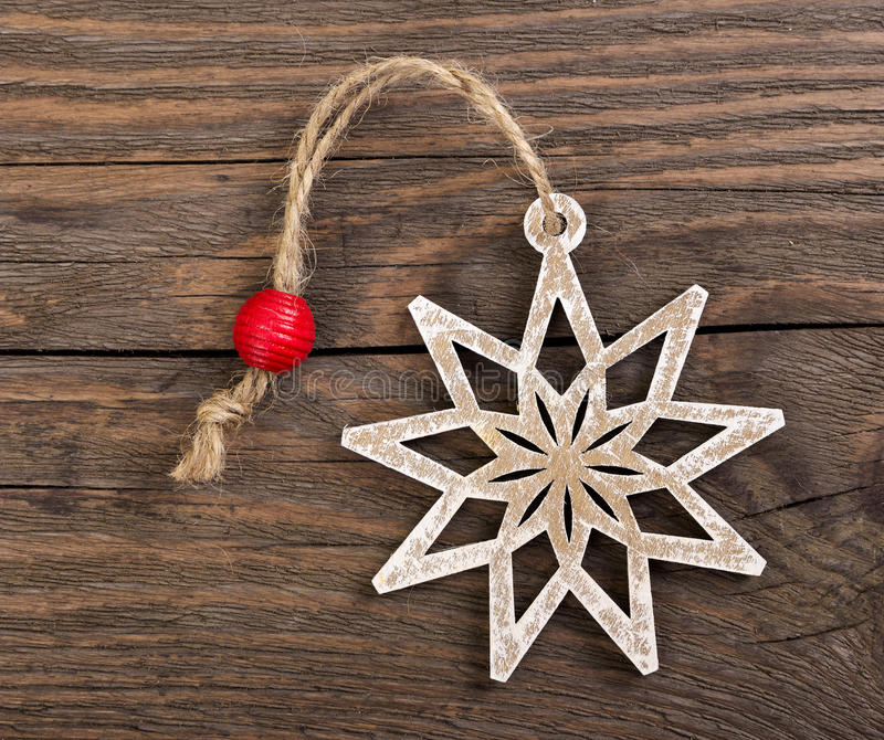 Wooden christmas snowflake decoration. On wooden background royalty free stock images