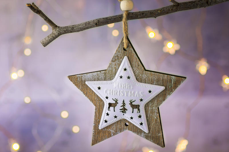Wooden Christmas star ornament with reindeers hanging on dry tree branch. Shining garland golden lights. Beautiful background royalty free stock photos