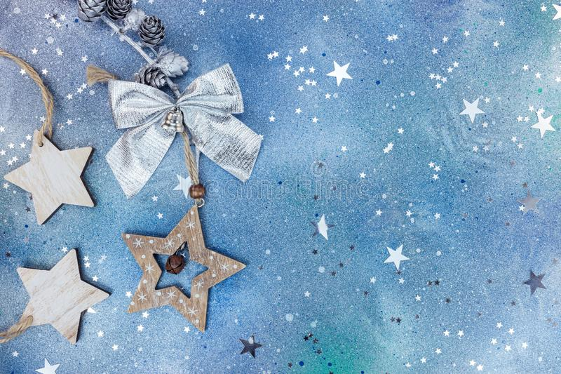 Wooden christmas star and silver bow on blue background. Star shaped wooden christmas decorations and silver bow on blue background royalty free stock photography