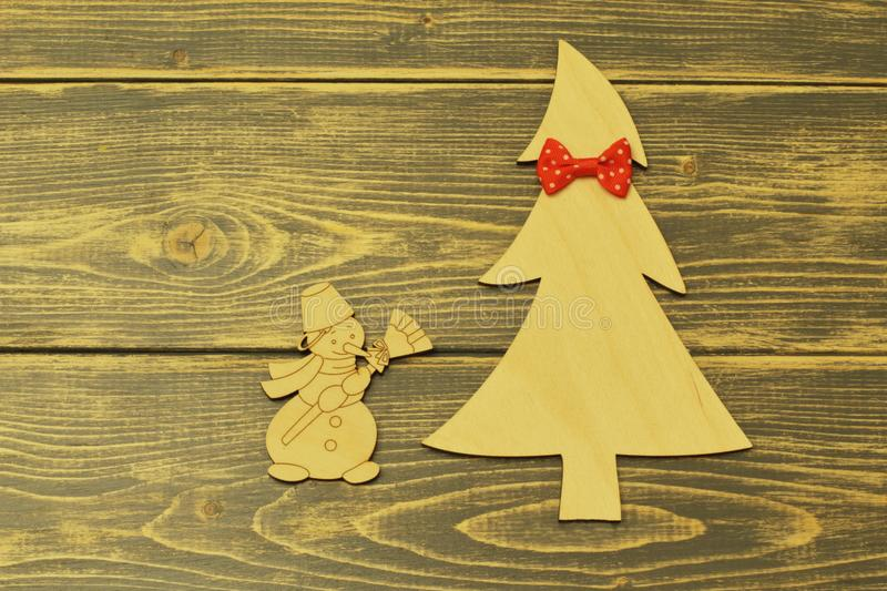 Wooden Christmas tree decorated with red bow tie and cheerful vintage snowman with broom on old wooden dark background stock photo