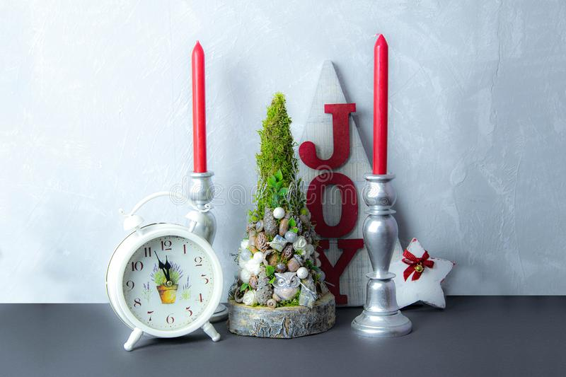 Wooden christmas tree and heart, red and white candlesticks on white door background. Christmas decoration stock photography