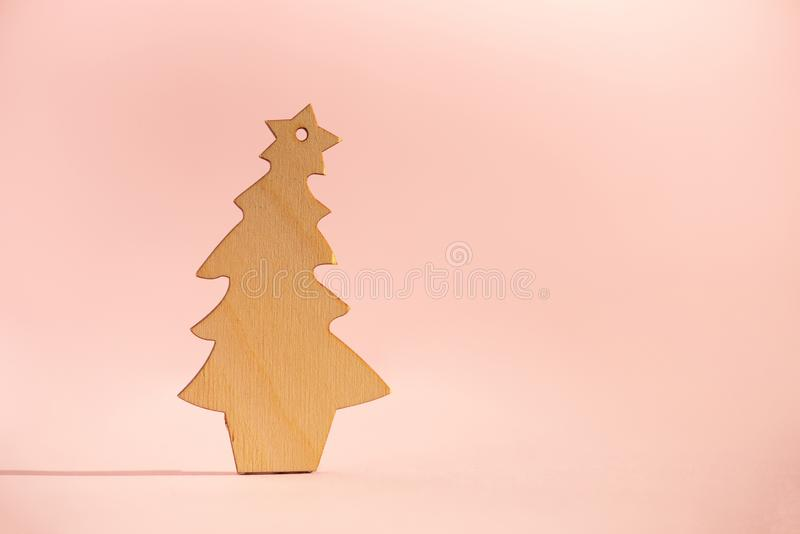Wooden Christmas tree on pink background with copy space. New Year party. Winter holiday concept. Greeting card in minimal style. Eco friendly decoration stock photos