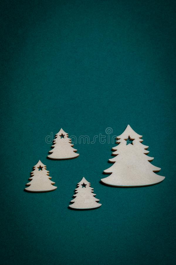 Wooden Christmas trees on Christmas green background stock photos
