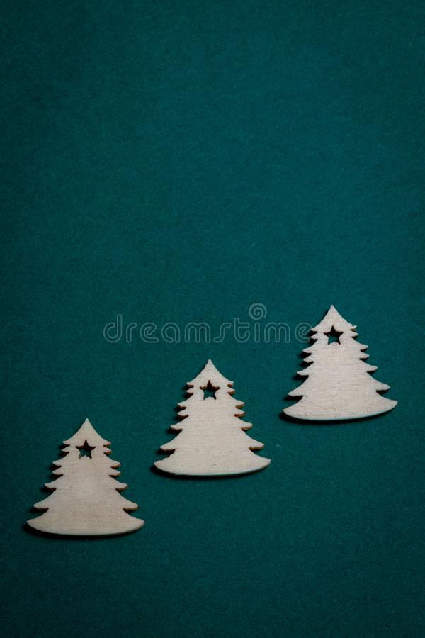 Wooden Christmas trees on Christmas green background stock images