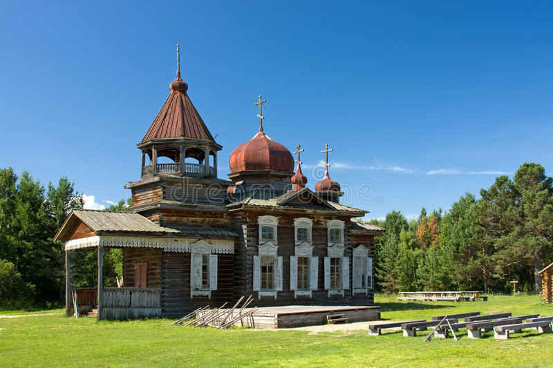 Wooden church. Antique old russian wooden church in the green forest royalty free stock image