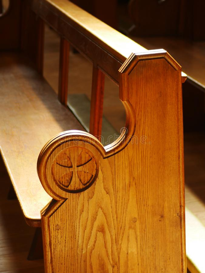 Wooden Church Pew. Light brown wooden church pew with cross decoration at end stock photography
