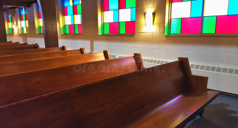Wooden church pews with stained glass windows stock images