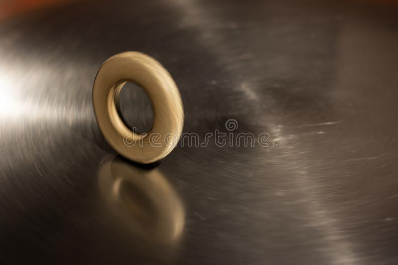 Wooden circle rolling on metal pad stock images