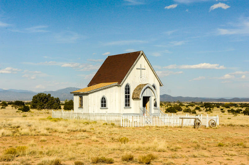 Wooden clapboard simple frame church in rural New Mexico. Wooden clapboard simple frame church in rural New Mexico with a cross over the doorway and a fence out stock photo