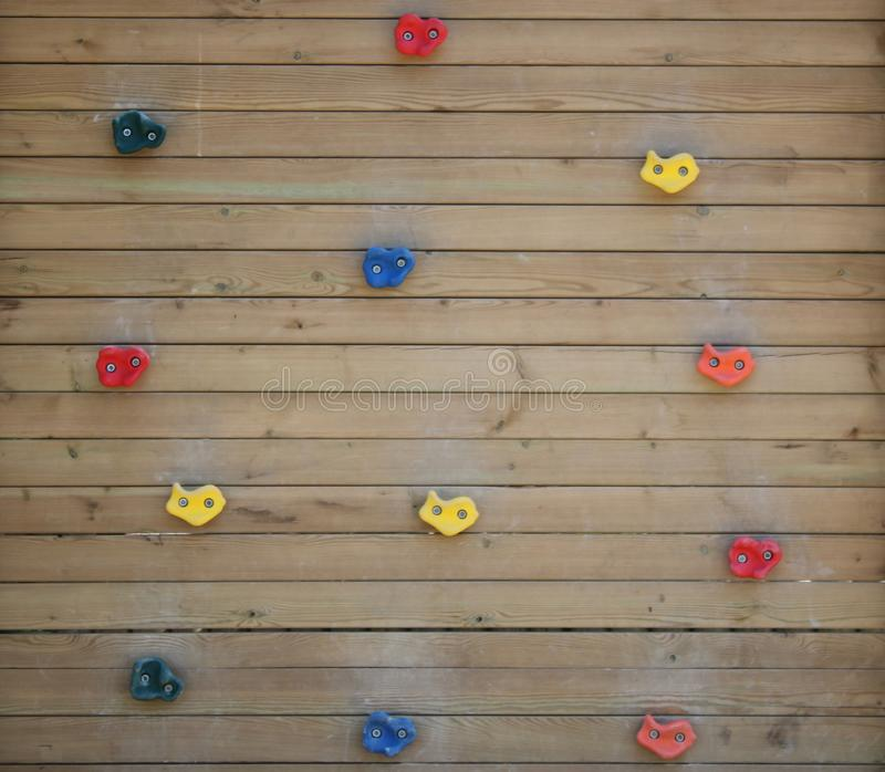 Wooden climbing wall. Colorful plastic parts. For kids. Child climbing warning sign in park, leisure, fun, rope, extreme, sport, exercise, safety, adventure stock image