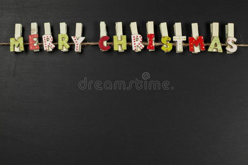 Wooden clips with Merry Christmas sighn on black background with stock image