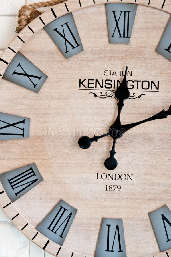 Wooden clockface on white wall stock image